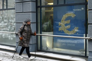 A woman passes by a poster that says. 'The euro is coming to Lithuania soon' in Vilnius, Lithuania, on Monday.