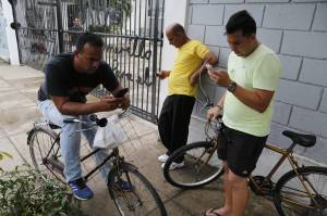 Cubans check their phones outside a center run by a Havana artist who offers his Wi-Fi network for free [Image Courtesy of Wall Street Journal]