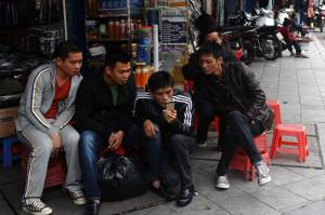 Men read news from a smartphone in downtown Hanoi, Vietnam [Image courtesy of WSJ]